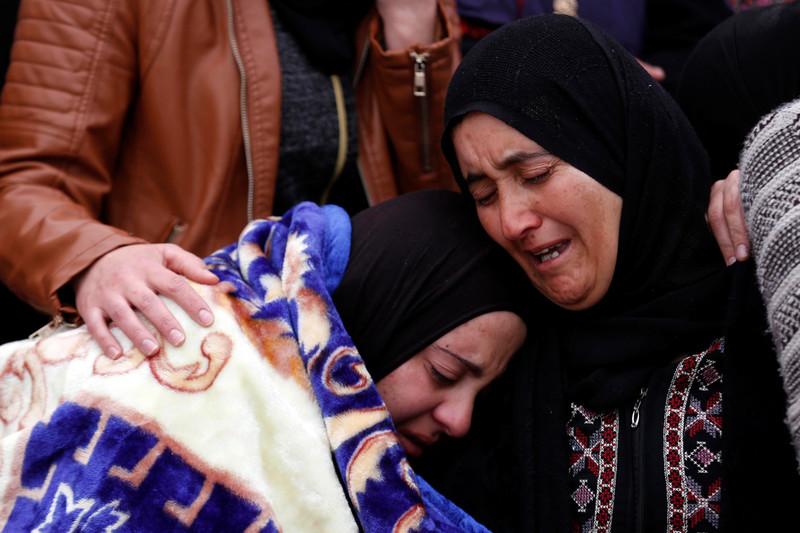 Two women embrace in tears