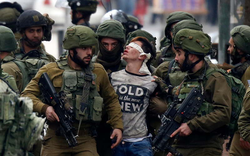 Soldiers arrest a blindfolded boy