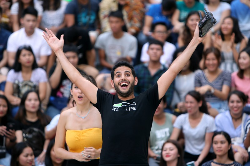 Man stands before crowd with arms wide open