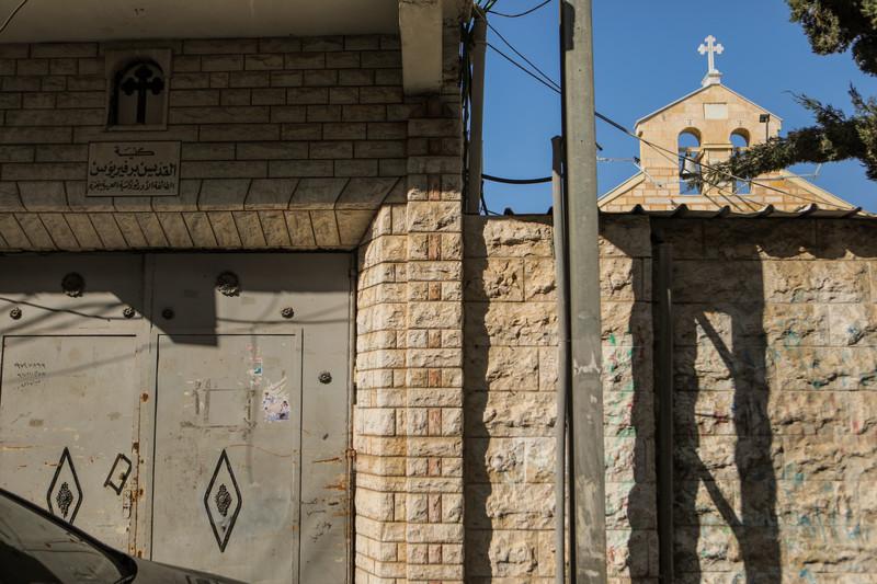 Church bells can be seen behind a shuttered metal door