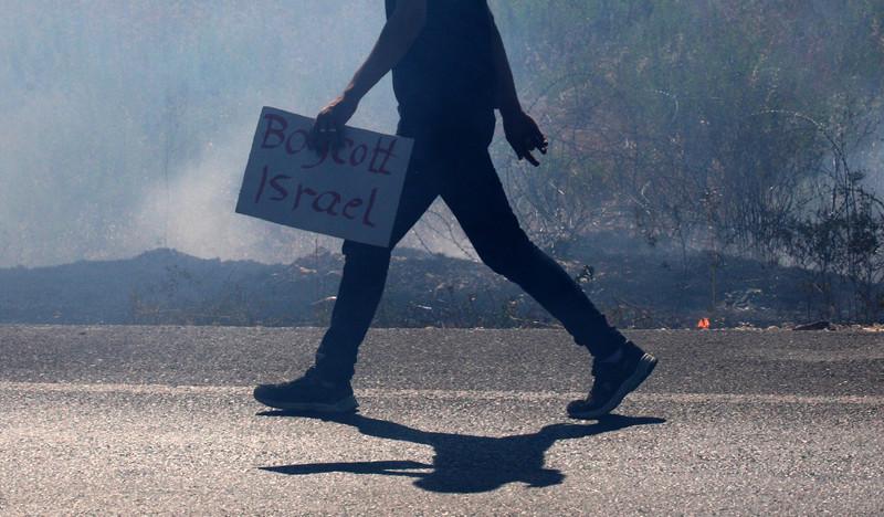 Silueta de una persona caminando con un cartel