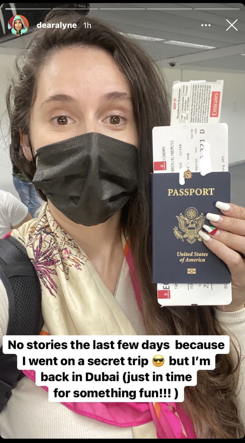 A woman holding a passport, wearing protective mask