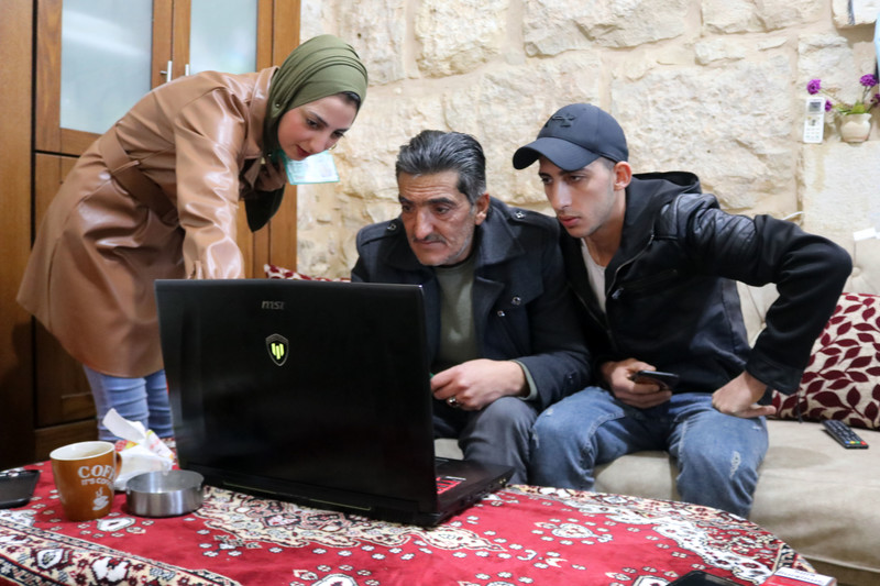 Two men and a woman stare at a laptop