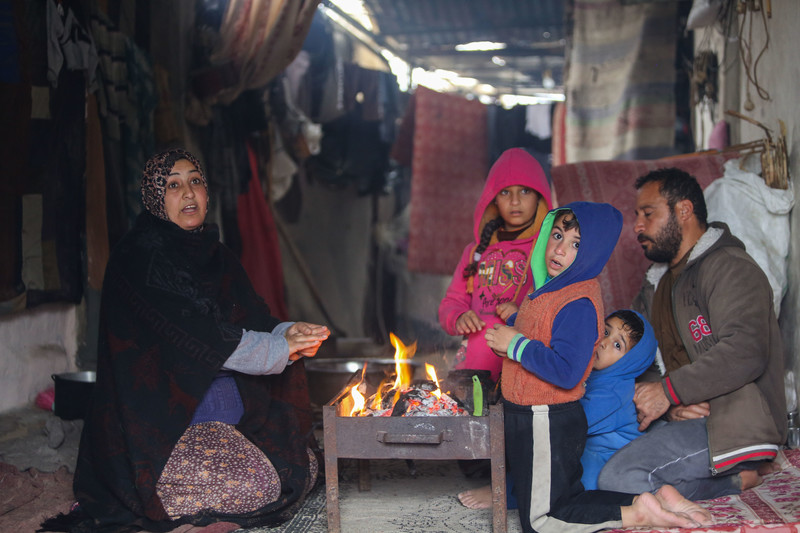 Two adults and two children warm their hands against a wood fire