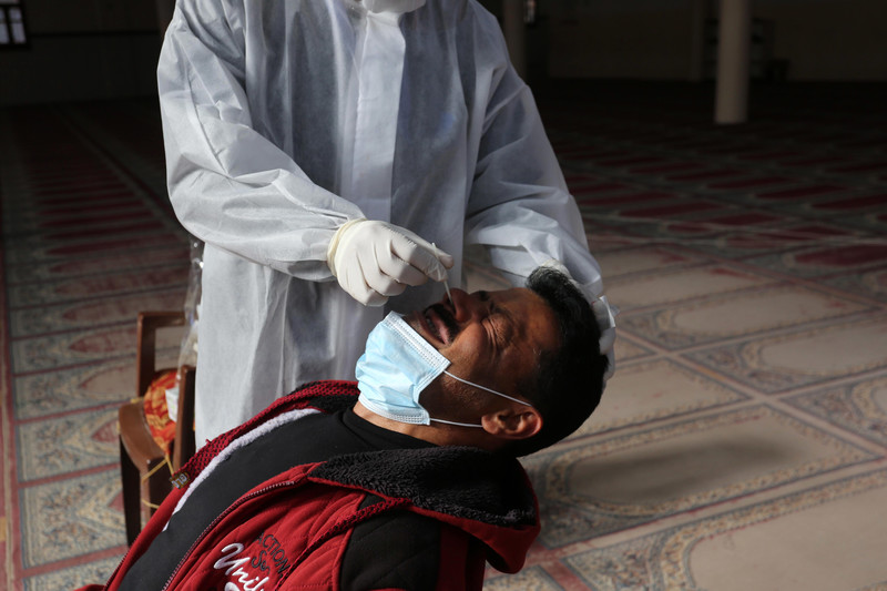 A man flinches as a medical worker in full protective gear swabs his nose