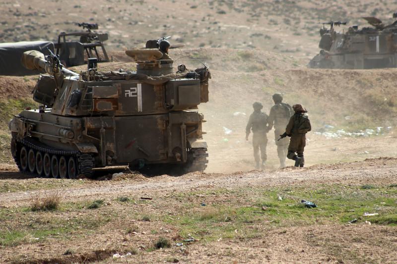 Soldiers walk near military tank