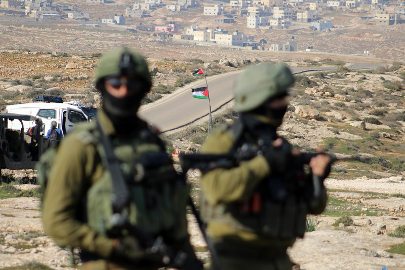 Two soldiers take position, Palestinian flag in the background