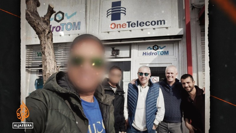 A group of men pose for a picture. Two faces are blurred