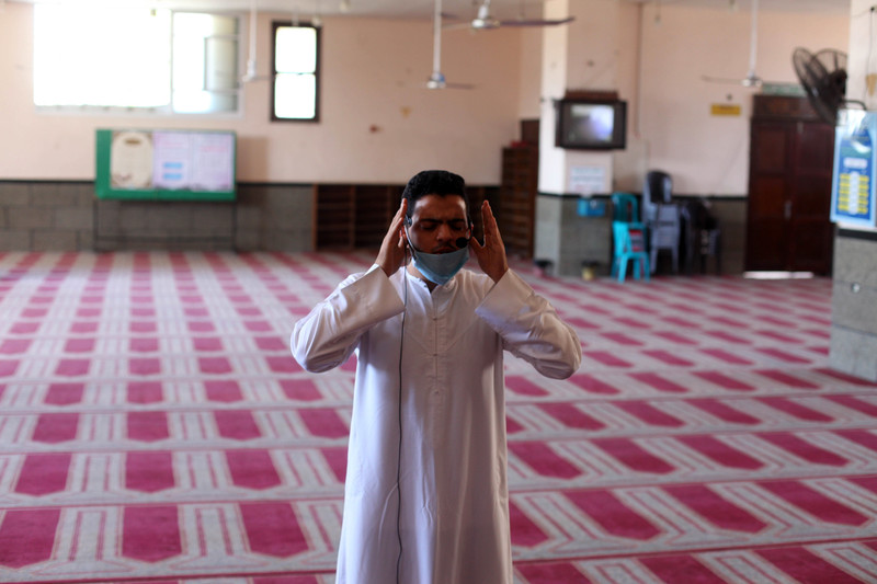A man raises his hands to his head in prayer in an otherwise empty room