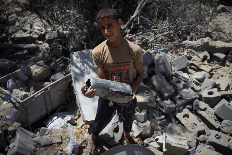 Boy holding metal object stands amid rubble
