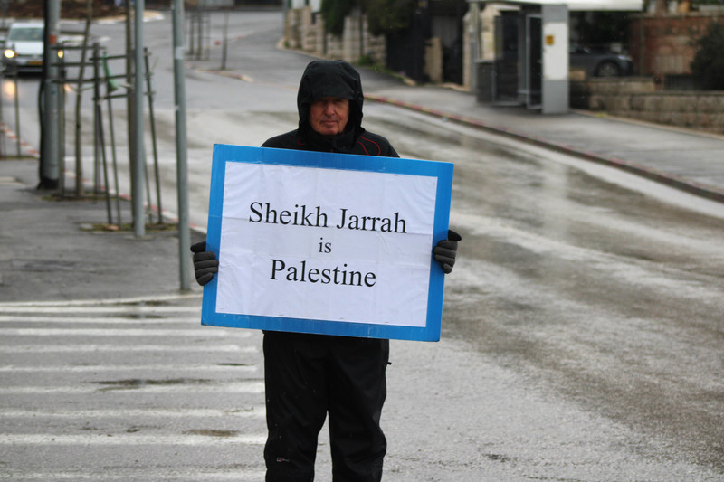 A person wearing a winter coat holds a sign in the street