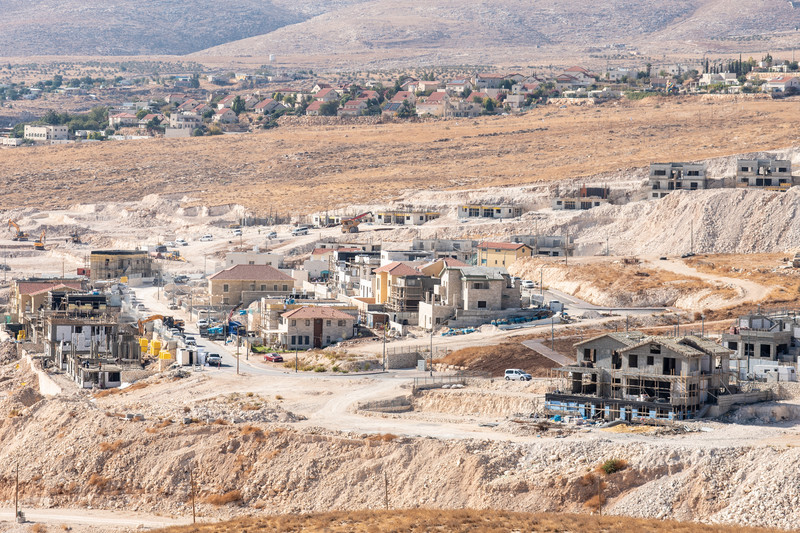 Broad view of unfinished buildings against arid landscape