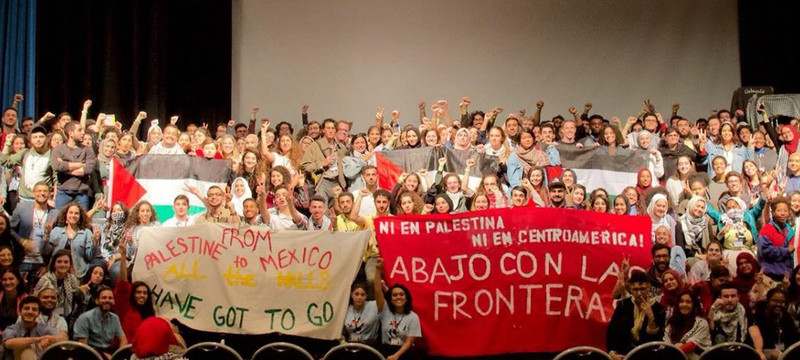 Activists gather on a stage and hold banners