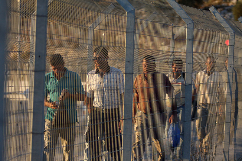 A group of men walk behind a metal fence