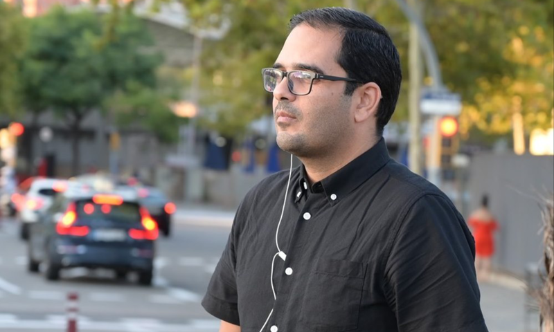 A man in a button-down shirt and earphone stands in the street