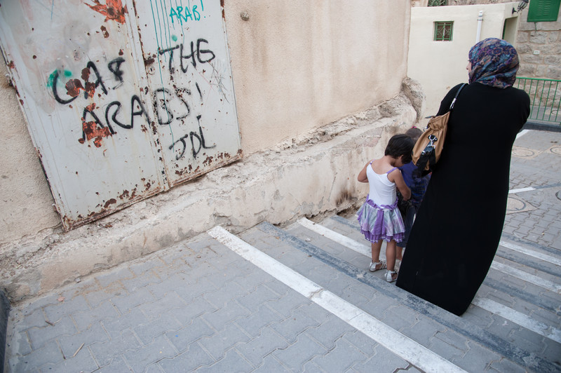 Woman and children walk past wall spray painted with graffiti reading Death to the Arabs!