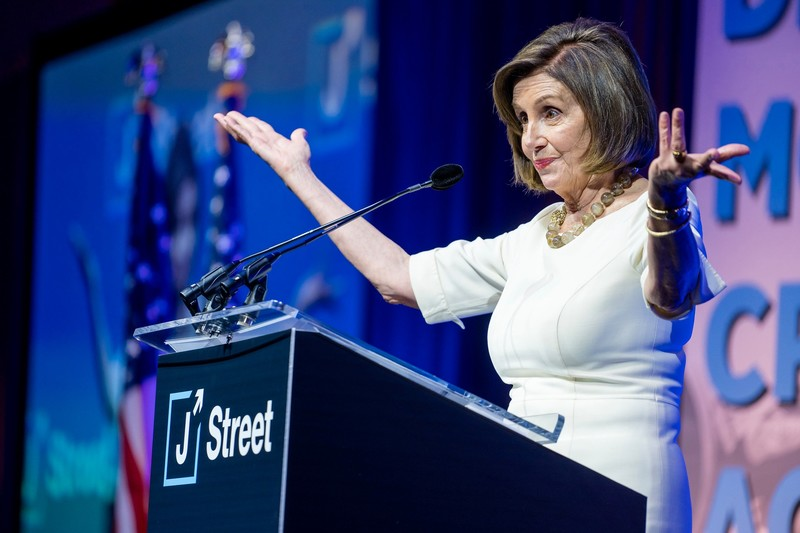 A woman stands at podium with arms outstreched