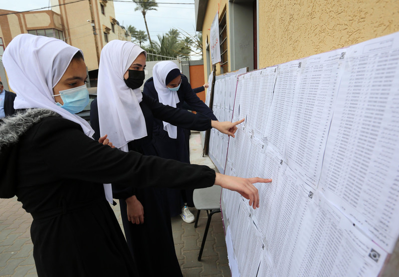 Women point to sheets of paper hung on notice boards