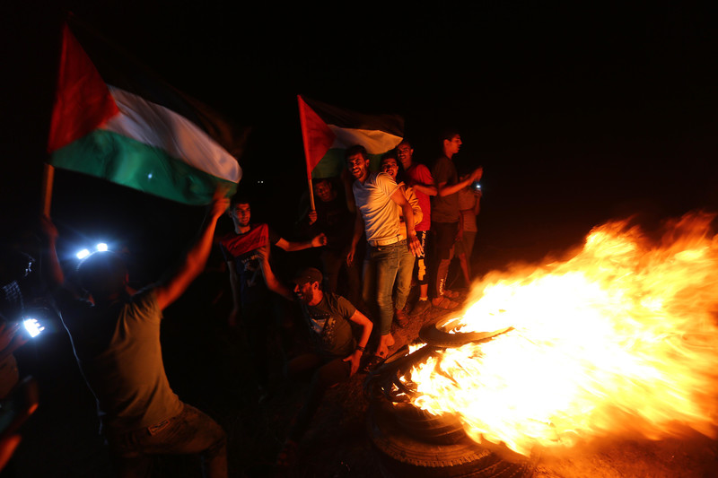 Young men smile while holding flags and standing next to a fire at night