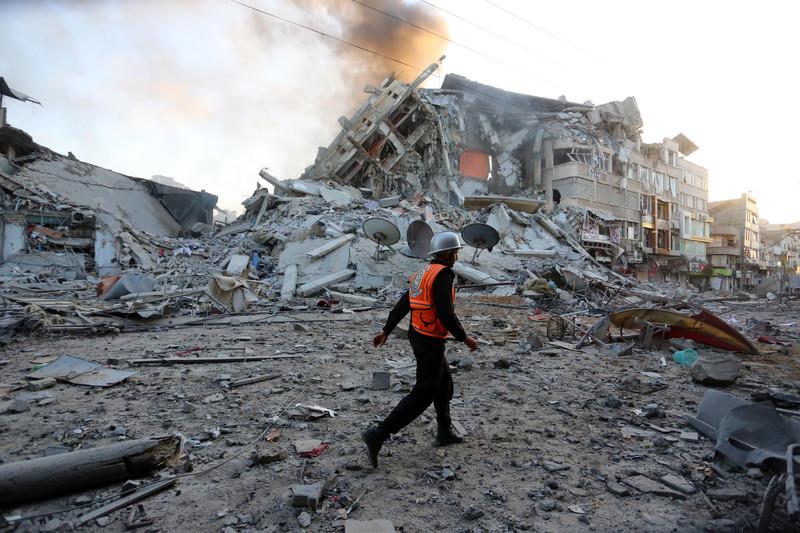 A man in an orange vest walks past the rubble of a building