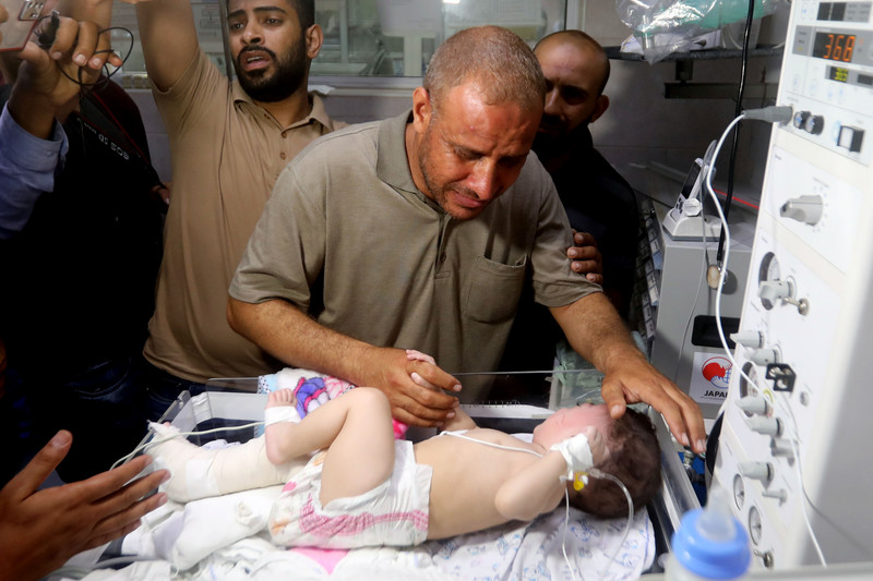 An emotionally distraught man caresses a baby lying in a hospital bed