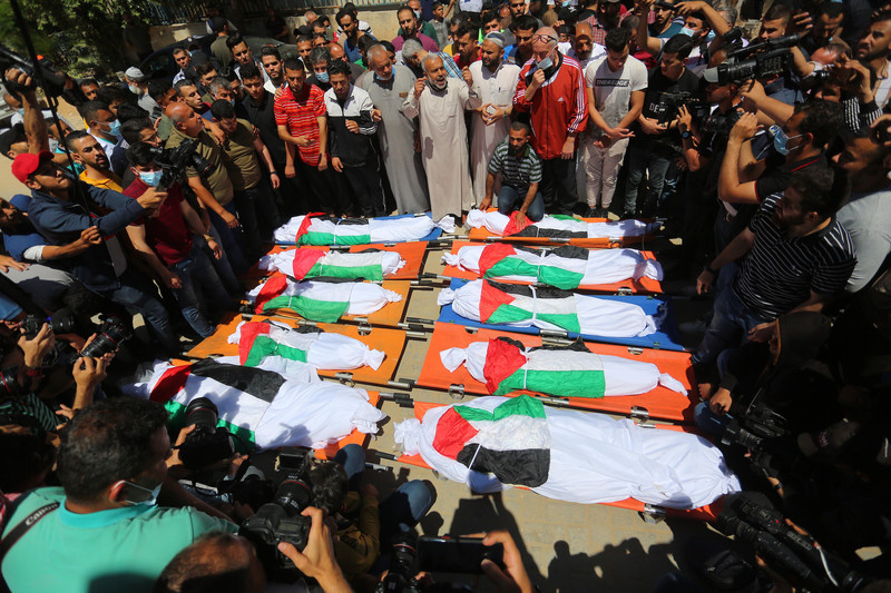 A crowd of men stand around ten bodies shrouded in Palestinian flags
