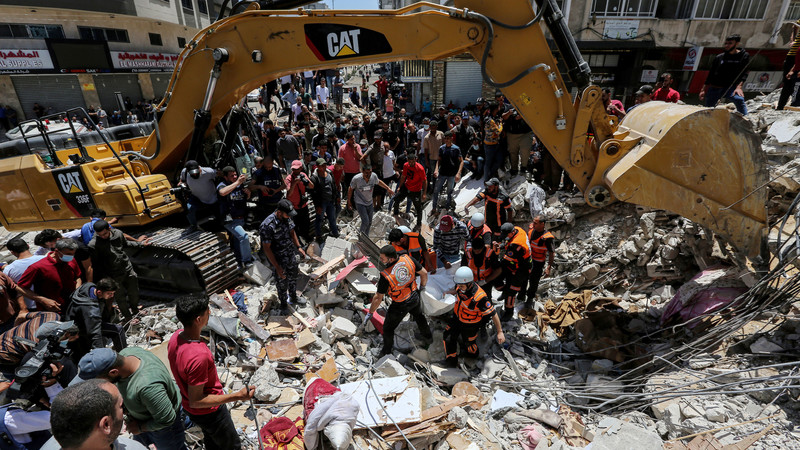 A crowd of people stand under an excavation machine on an urban street