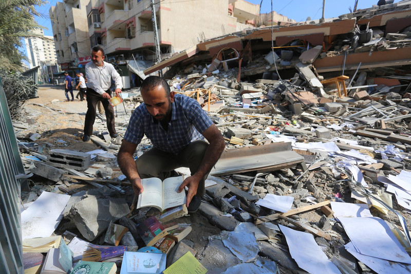 A man kneeling on the ground holds an open book in his hands amid rubble from a collapsed building