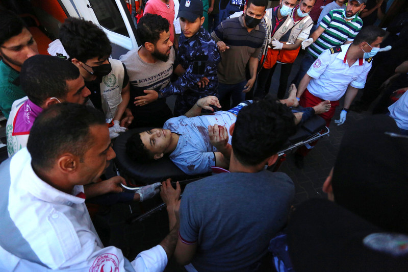 A young man with bloodied clothes lies on a stretcher amid crowd next to ambulance