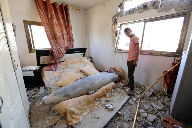 Youth looks at missile that landed on bed in debris-strewn room