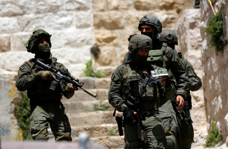 Four heavily armed Israeli soldiers stand near stone building