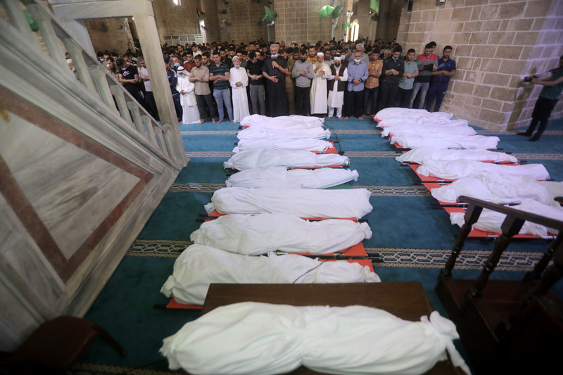 People pray at the mosque over 17 bodies wrapped in white cloth