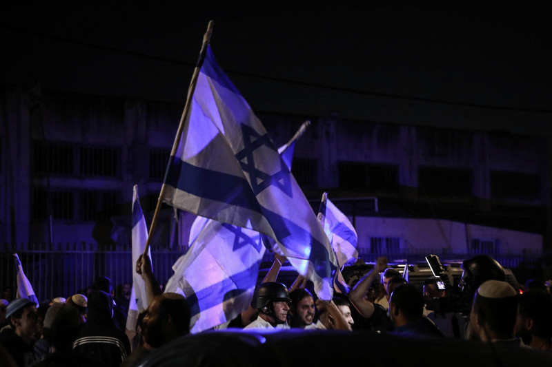 Protesters wave Israeli flags during the night