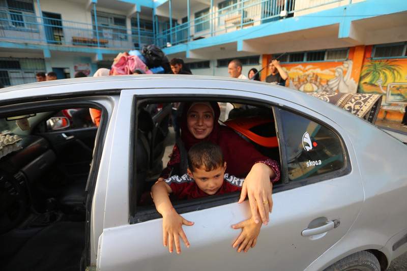Woman and boy smile while looking out of car in front of UN school