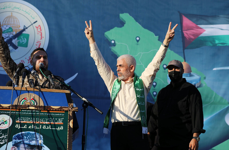 Yahya Sinwar raises arms in air and makes V for victory hand gesture while standing on stage