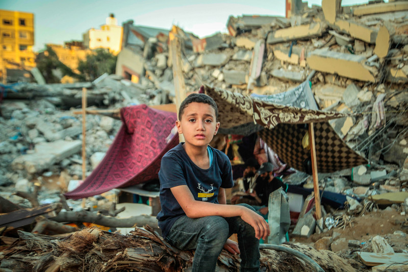 Boy sits on rubble in front of makeshift tent amid destroyed buildings