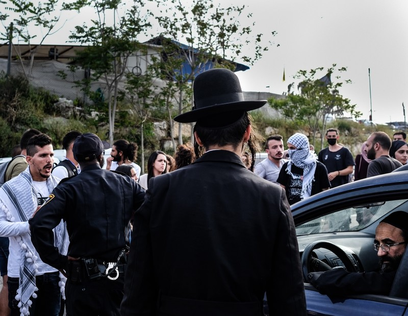 A man argues with a policeman as onlookers stand around