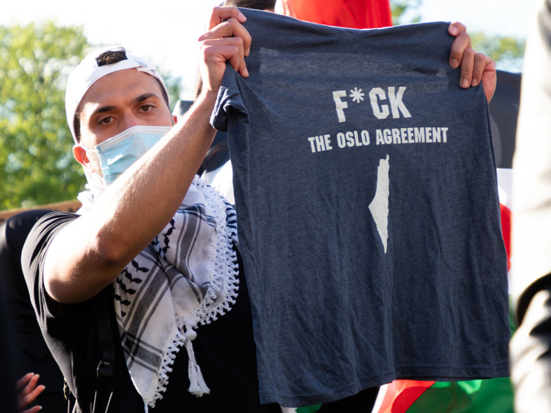 Man wearing kuffiyeh around his neck holds up T-shirt reading F*CK the Oslo agreement