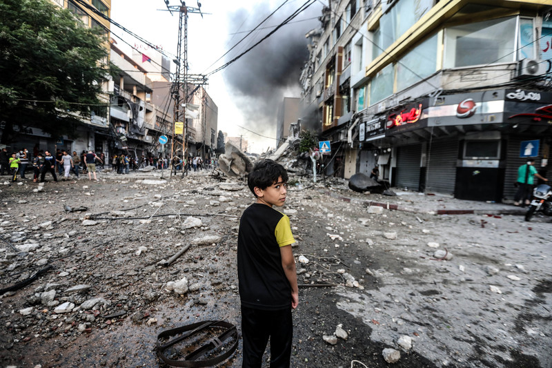 A boy stands in debris-strewn street with smoke on the horizon