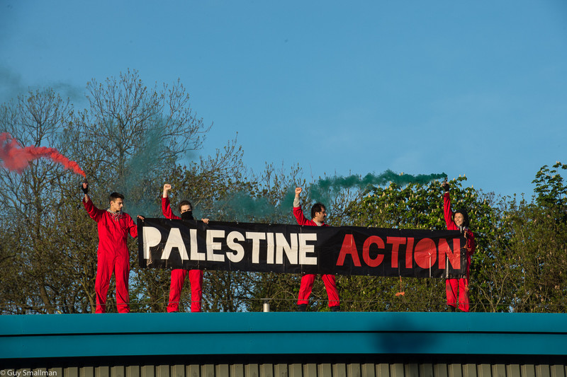 """Four red-suited people hold a banner reading """"Palestine Action"""""""
