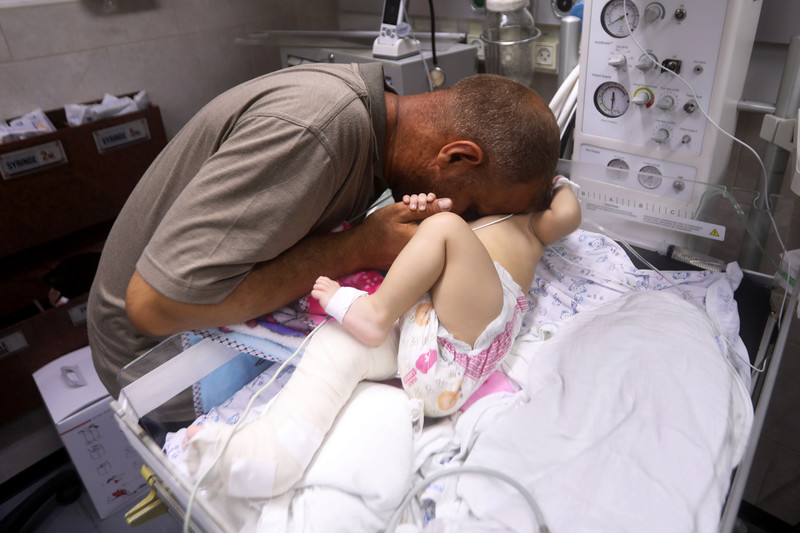 Man leans over and embraces child on a hospital bed
