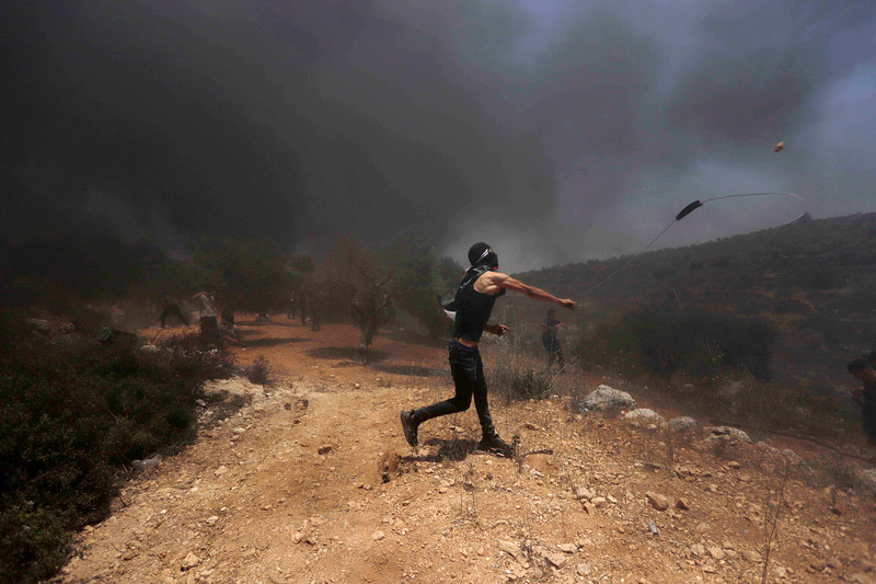 Standing in a smoke-filled field, a masked protester hurls a stone with a slingshot
