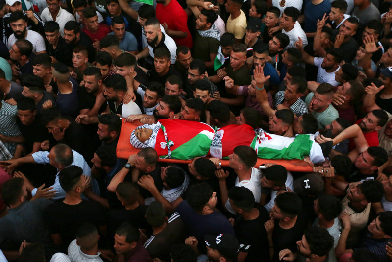 A large crowd of mourners carry a body wrapped in a Palestinian flag on a stretcher