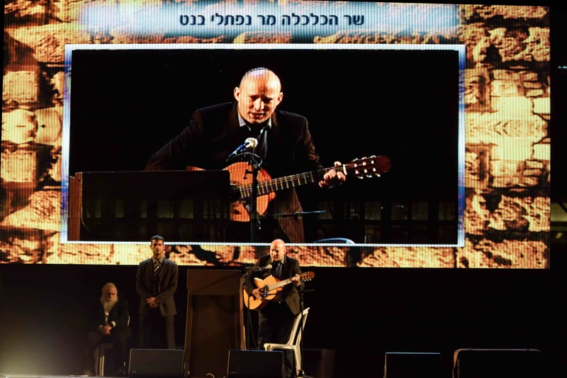 A giant screen shows one man playing a guitar as three people stand on stage beneath