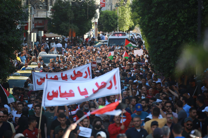 Large crowd of demonstrators holding two large banners, flags