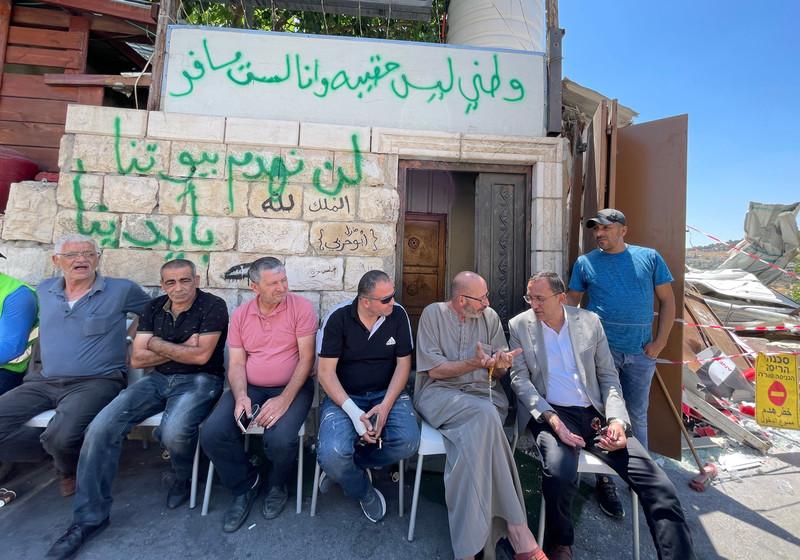 Seven men sit in front of a graffitied building, near rubble