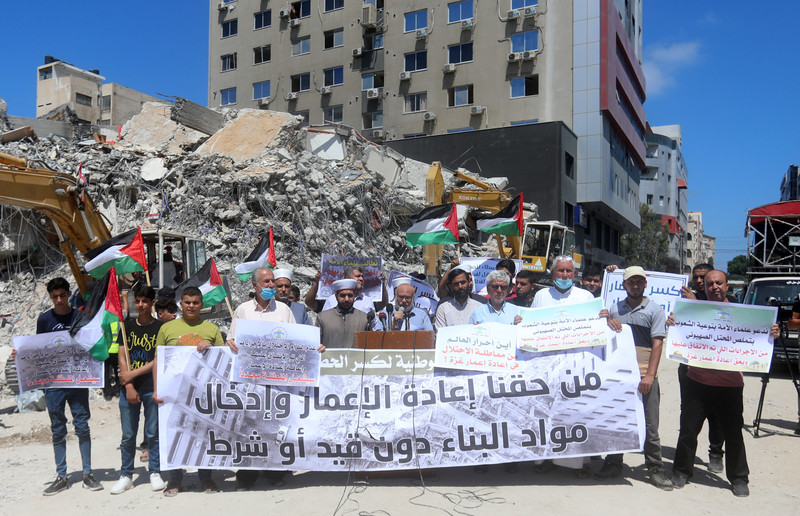 People hold banners and flags before a podium against a background of rubble