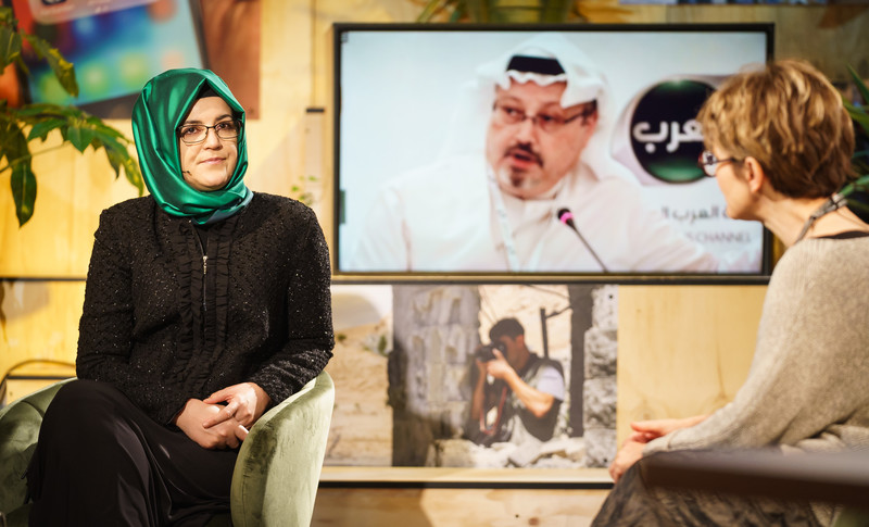 Two women in chairs converse front of screen that shows Jamal Khashoggi