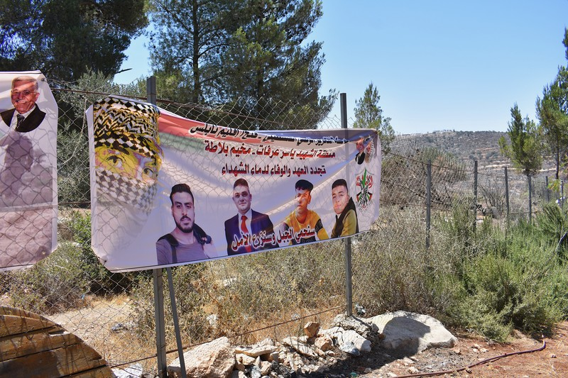 A banner depicting four young men hangs on a fence