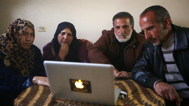Four people sit in front of laptop